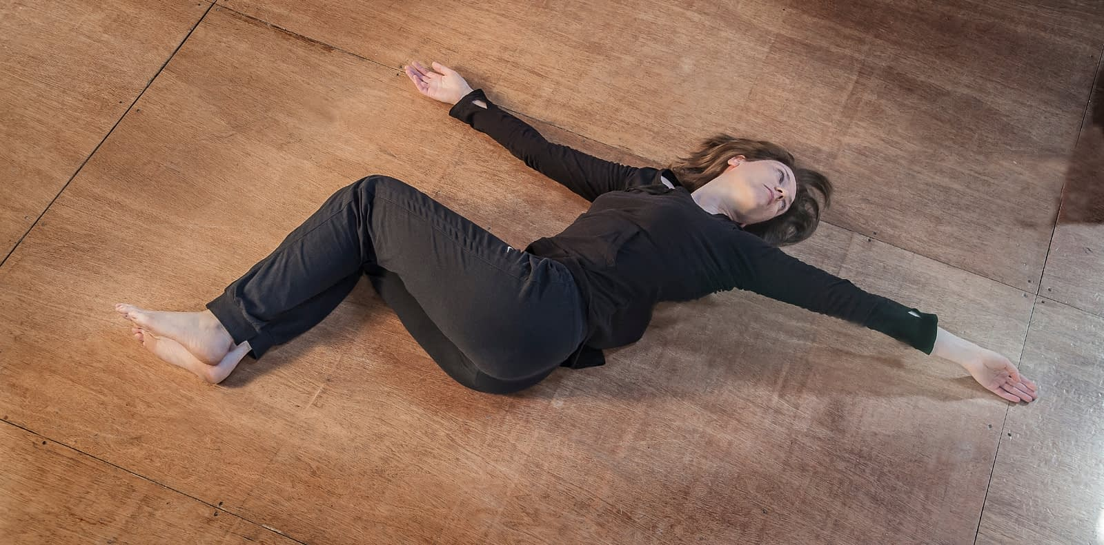 Woman on floor hands streched. Legs bent, one on the other.